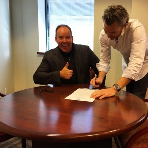 Trevor Linden signs the contract